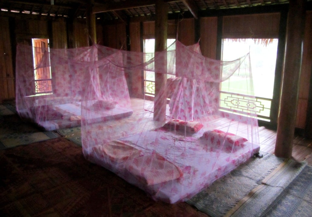 Sleeping on the wooden floor under mosquito nets