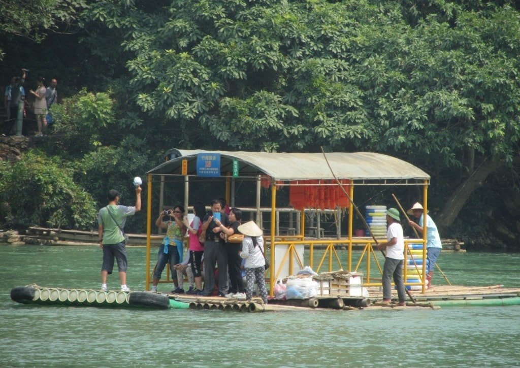 A Vietnamese floating vendor approaches a raft of Chinese tourists
