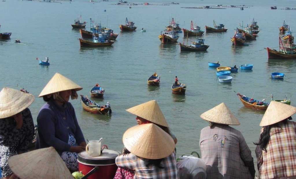 Women gather at dawn to meet the fishing boats, Mui Ne