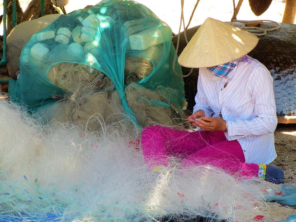 Mending fishing nets on Bãi Rạng Beach, Quy Nhon, Vietnam