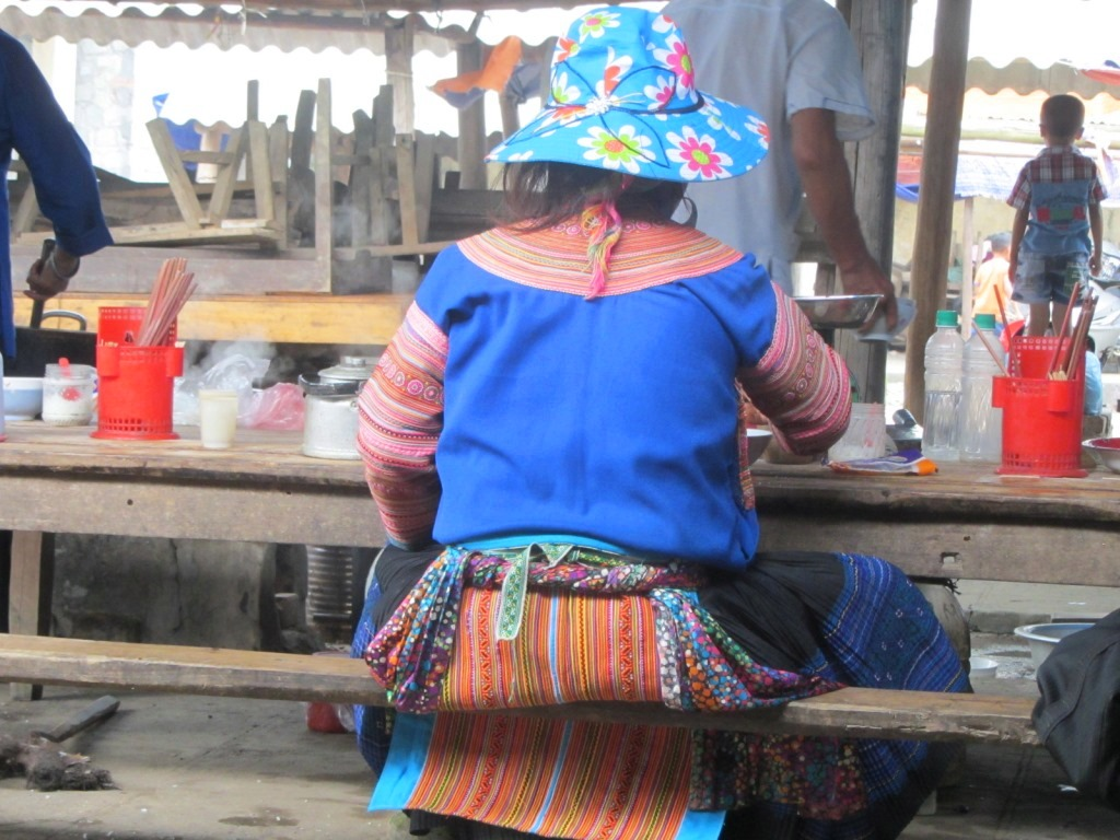 A woman sits for breakfast at Hoang Su Phi Market