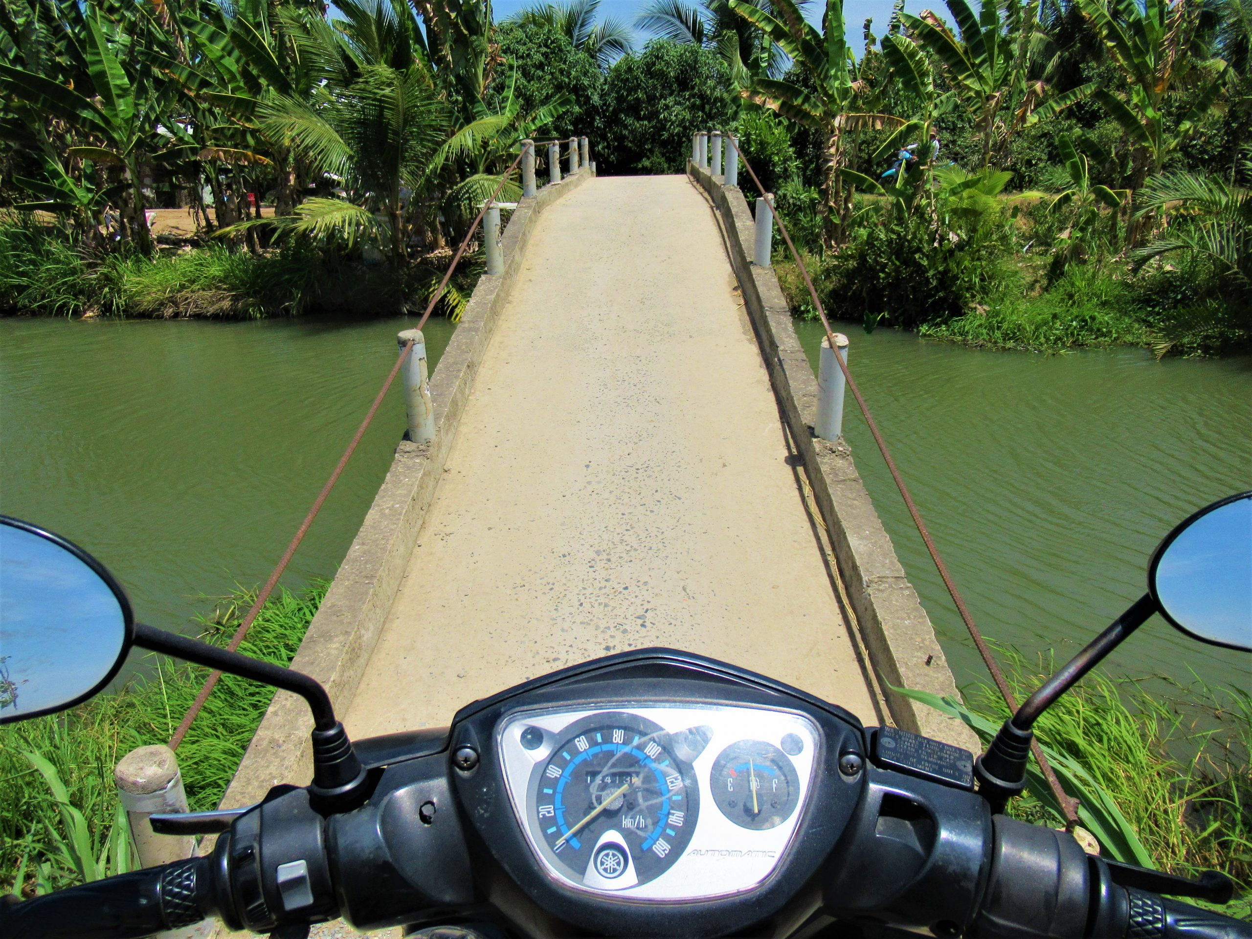 Crossing a canal on a narrow concrete bridge on the Temple-Hopping Loop, Mekong Delta